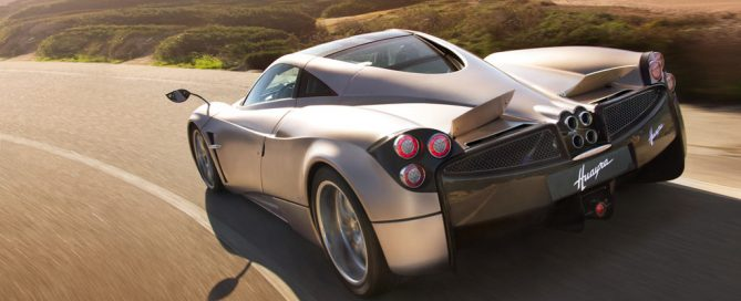 The Pagani Huayra, silver, drives along a windy country road with the sun bearing down overhead.