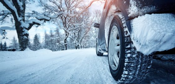 Car tire drives down winter road.