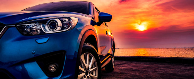 Luxury car parked near beach during sunset